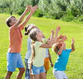 Group of children  jumping together on green grass in park Royalty Free Stock Photo