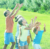 Group of children  jumping together on green grass in park. Group of laughing cheerful children having fun and jumping together on green grass in park Stock Photo