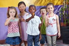 Group of children in kindergarten. Interracial group of children in a kindergarten eating suckers Royalty Free Stock Image