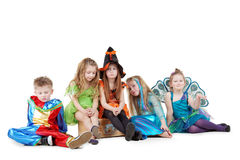 Group of children in masquerade costumes sits Royalty Free Stock Photography