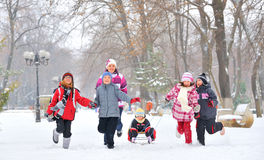 Group of children and mother playing on snow in winter time Royalty Free Stock Images