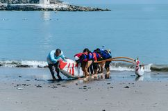 A group of children paddlers pulling a boat towards the shore a summer day. A group of boys paddlers pulling a boat towards the shore Stock Photo