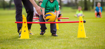 Group of children at physical education class. Coach and young boy exercising with ball on a green grass Royalty Free Stock Images
