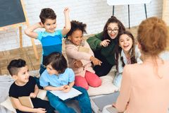 Group of children play a quiz with teacher in peach blouse while in primary school class. Royalty Free Stock Photography
