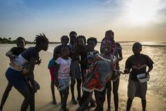 Group of children playing by the beach in the island of Orango at sunset, in Guinea Bissau. Orango is part of the Bijagos Archipelago royalty free stock images