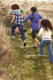 Group Of Children Playing In Field Together Stock Photo