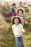 Group Of Children Playing In Field Together. In the sun Stock Photo
