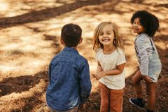 Group of children playing in forest. Beautiful girl with friends in a park. Group of children playing in forest royalty free stock photos
