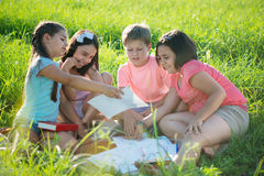 Group of children playing on grass Stock Photos