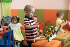 Group of children playing in kindergarten or daycare centre Stock Photos