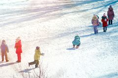 Group of children playing on snow in winter time. Togetherness, vacations, kid Stock Photo