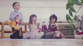 A group of children playing stuffed toys. A group of children sitting on the floor and playing stuffed toys. Two girls and boy stock footage