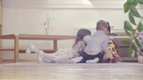 A group of children playing stuffed toys. A group of children sitting on the floor and playing stuffed toys. Two girls and boy stock video footage