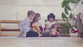 A group of children playing stuffed toys. A group of children sitting on the floor and playing stuffed toys. Two girls and boy stock video