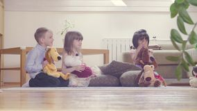 A group of children playing stuffed toys. A group of children sitting on the floor and playing stuffed toys. Two girls and boy. One girl looks upset stock video