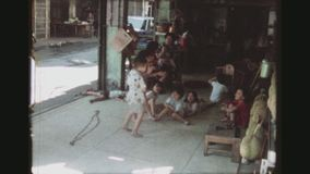 Group Of Children Playing. THAILAND, BANGKOK, MAY 1978. A Group Of Small Children Running, Singing And Clapping Their Hands In A Rundown Vegetable Shop, With Two stock video footage