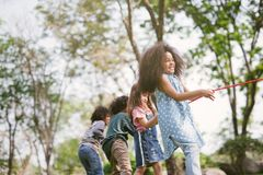 Group of children playing tug of war at the park. stock image