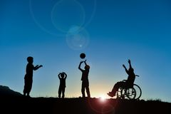 Group of children playing. A group of children, of which one sitting in a wheelchair playing with a ball outdoors stock images
