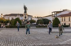 Group of children plays with a ball in the Plaza de Hernan Cortes with the statue of the Conquistador in the background royalty free stock photography