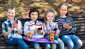 Group of children posing with mobile devices Stock Photo