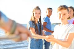 Children pulling rope during tug of war game on beach. Summer camp. Group of children pulling rope during tug of war game on beach. Summer camp Stock Image