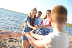 Group of children pulling rope during tug of war game on beach. Summer camp. Group of active children pulling rope during tug of war game on beach. Summer camp Royalty Free Stock Image
