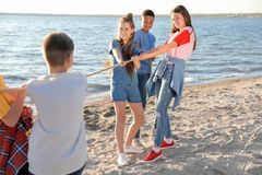 Group of children pulling rope during tug of war game on beach. Summer camp. Group of active children pulling rope during tug of war game on beach. Summer camp Stock Photo