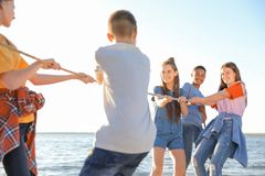 Group of children pulling rope during tug of war. Game on beach. Summer camp Royalty Free Stock Photos