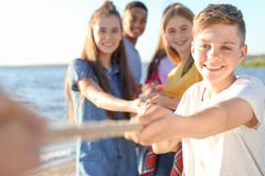 Group of children pulling rope during tug of war game. On beach. Summer camp Stock Image
