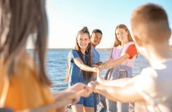 Group of children pulling rope during tug of war game. On beach. Summer camp Stock Photos