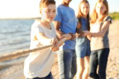 Group of children pulling rope during tug of war. Game on beach. Summer camp Royalty Free Stock Photo