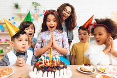 Group of children rejoice of cake with burning candles on occasion of birthday. Royalty Free Stock Photos