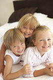 Group Of Children Relaxing On Bed Stock Image