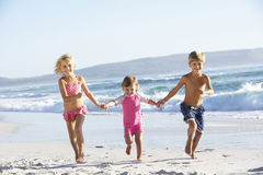 Group Of Children Running Along Beach In Swimwear Stock Photography