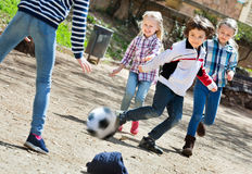 Group of children running after ball. Group of cheerful positive children running after ball in urban location Royalty Free Stock Photography