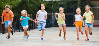 Group of  children running outdoors in city street. Group of cheerful smiling glad children running outdoors in city street on good weather Royalty Free Stock Image