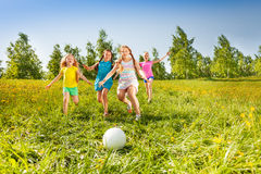 Group of children running to the ball in meadow Royalty Free Stock Photo