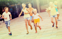 Group of children running together in town on summer. Group of children in school age running together in town on summer Stock Images