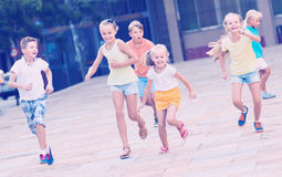 Group of children running together in town on summer. Group of children in school age running together in town on summer Royalty Free Stock Photography