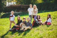 A group of children of school and preschool age are sitting on the green grass in the park. A group of happy smiling children of school and preschool age are royalty free stock images