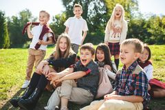 A group of children of school and preschool age are sitting on the green grass in the park. A group of happy smiling children of school and preschool age are stock image
