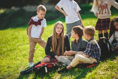 A group of children of school and preschool age are sitting on the green grass in the park. A group of happy smiling children of school and preschool age are royalty free stock image