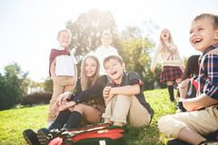 A group of children of school and preschool age are sitting on the green grass in the park. A group of happy smiling children of school and preschool age are stock photos