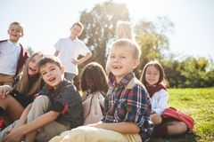 A group of children of school and preschool age are sitting on the green grass in the park. A group of happy smiling children of school and preschool age are stock photo
