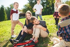A group of children of school and preschool age are sitting on the green grass in the park. A group of happy smiling children of school and preschool age are royalty free stock photography