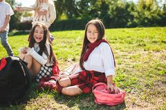 A group of children of school and preschool age are sitting on the green grass in the park. A group of happy smiling children of school and preschool age are stock photography