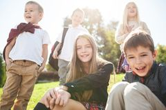 A group of children of school and preschool age are sitting on the green grass in the park. A group of happy smiling children of school and preschool age are royalty free stock photos