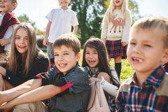 A group of children of school and preschool age are sitting on the green grass in the park. A group of happy smiling children of school and preschool age are stock images