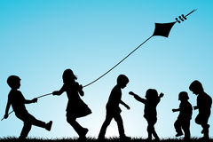 Group of children silhouettes with a kite outdoor Stock Images
