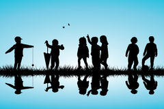 Group of children silhouettes playing outdoor near Royalty Free Stock Photography